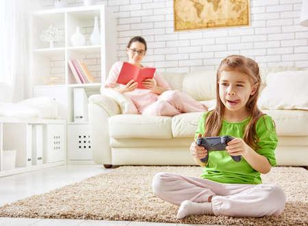 jugando videojuegos: familia relajarse. madre leyendo un libro, niño jugando juegos de video.