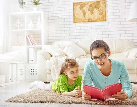 mujer leyendo libro: bastante joven madre leyendo un libro a su hija Foto de archivo
