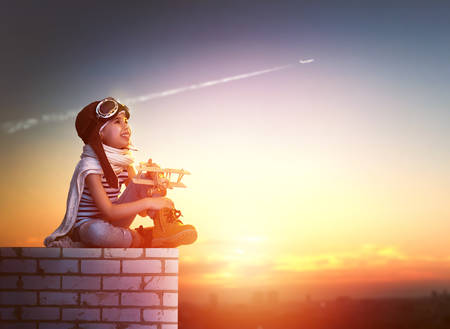 airplane: a child plays with a toy airplane in the sunset and dreams of becoming a pilot