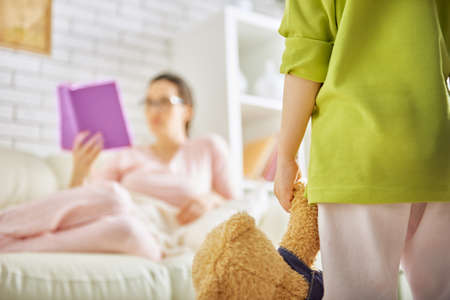 indifferent: child wants to play with mom, but she reads a book Stock Photo