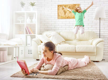 personas saltando: Familia relajarse. Madre leyendo un libro y el niño saltando en el sofá.