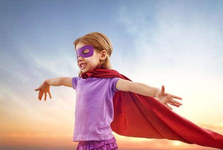 toddler: a little girl plays superhero Stock Photo