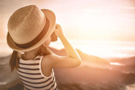při pohledu na fotoaparát: roztomilá holčička pořizuje snímky přírody