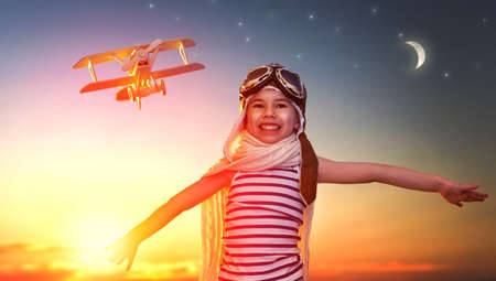 motivation: dreams of flight! child playing with toy airplane against the sky at sunset Stock Photo