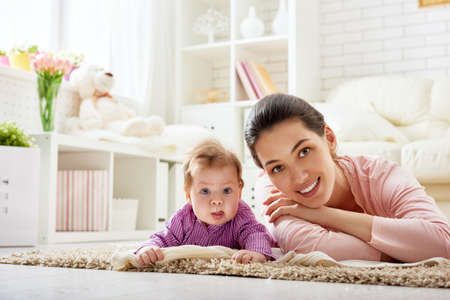 family sofa: mother playing with her baby in the living room