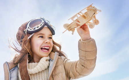 happy child girl playing with toy airplane. the dream of becoming a pilot Фото со стока