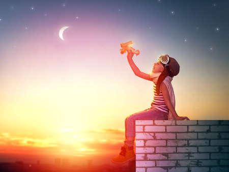 een kind speelt met een stuk speelgoed vliegtuig in de zonsondergang en droomt ervan om een pilot- Stockfoto