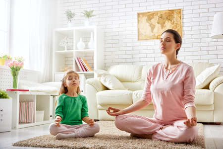 a young family: beautiful girl is engaged in yoga with her daughter