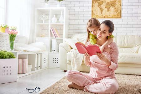 mooie jonge moeder het lezen van een boek aan haar dochter