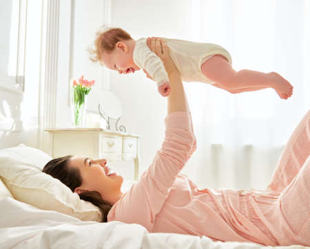 mother baby: happy family. mother playing with her baby in the bedroom.