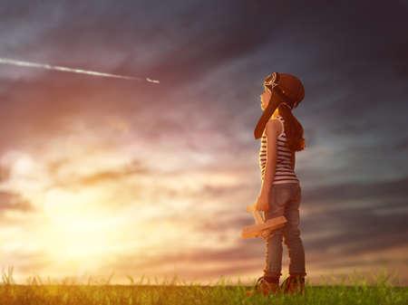 flug: Träume von Flug! Kind spielt mit Spielzeug-Flugzeug gegen den Himmel bei Sonnenuntergang