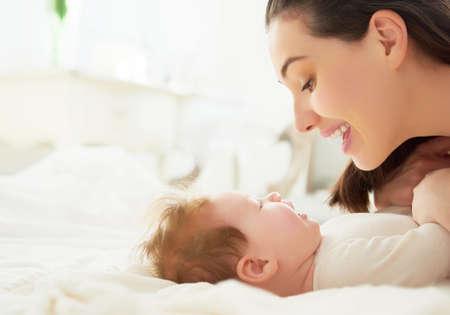 niñas bonitas: familia feliz. madre jugando con su bebé en el dormitorio. Foto de archivo