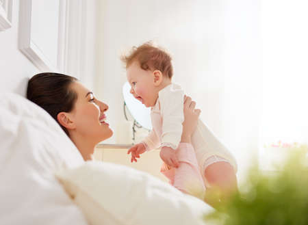 mother with baby: happy family. mother playing with her baby in the bedroom.
