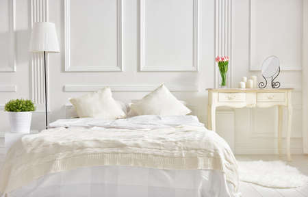 bedroom in soft light colors. big comfortable double bed in elegant classic bedroom Stok Fotoğraf