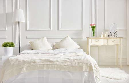 cama: dormitorio en colores claros suaves. gran cama doble en dormitorio elegante clásica Foto de archivo