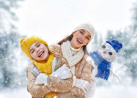 winter park: Happy family! Mother and child girl on a winter walk in nature. Stock Photo