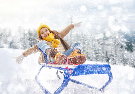Child sledding. Little girl enjoying a sleigh ride. Child girl riding a sledge. Child plays outdoors in snow. Outdoor fun for family winter vacation. Banque d'images