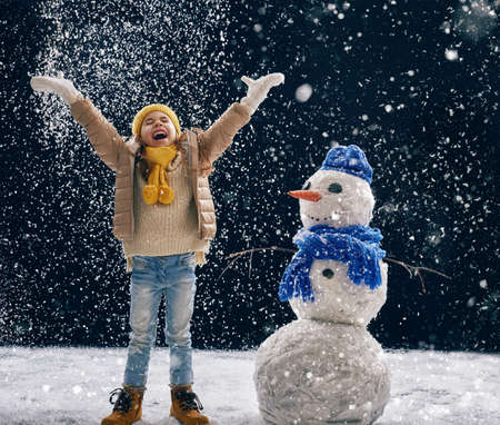 snow  snowy: happy child girl plaing with a snowman on a snowy winter walk. Little girl enjoys the game. Child girl playing outdoors in snow. Outdoor fun for winter vacation. Stock Photo