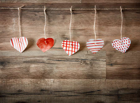 Paper hearts on wooden background.