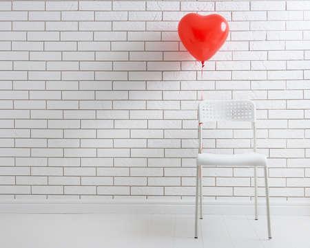 happiness: globo rojo en forma de corazón en el fondo de una pieza de paredes de ladrillo blanco.
