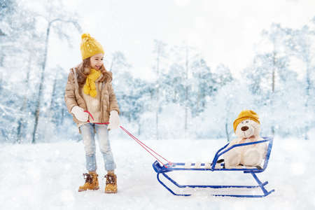 child smile: happy child girl plaing with a toy on a snowy winter walk. child rolls a teddy bear on a sled