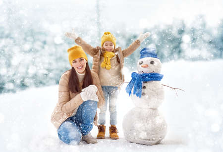 walk in: Happy family! Mother and child girl on a winter walk in nature. Stock Photo