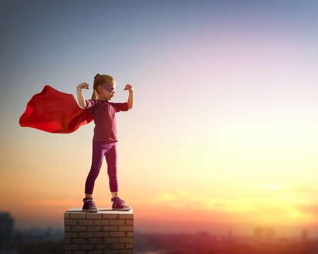 概念: 小孩子的女孩扮演的超級英雄。兒童在夕陽的天空背景。女孩動力概念