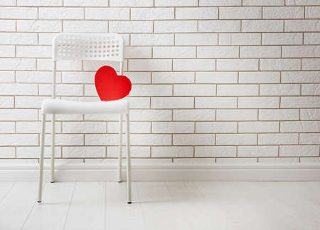 red gift box in shape of heart on the background of a blank white brick walls. the concept of love and Valentine's day.