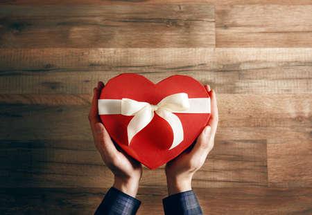 saint valentin coeur: m�le, mains tenant un cadeau sous la forme d'un c?ur. le concept de l'amour et la Saint-Valentin Banque d'images