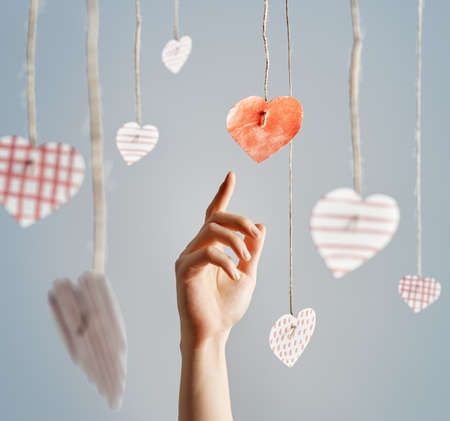 hand reaching: Mans hand reaching for paper hearts. Love, Valentine Day concept.
