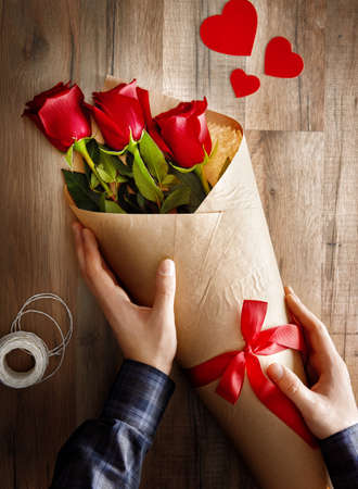 feeling happy: Male hands holding red roses on wooden background. the concept of love and Valentines day. Stock Photo
