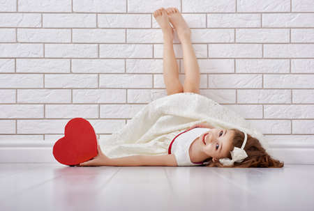 dia: Niño de la muchacha dulce con el corazón rojo. Niña feliz con el regalo de San Valentín en una pared de ladrillo blanco. La boda, el concepto de San Valentín.