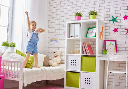 child laughing: funny child girl plays at home. girl having fun and dancing on the bed. recreation and entertainment at home. Stock Photo
