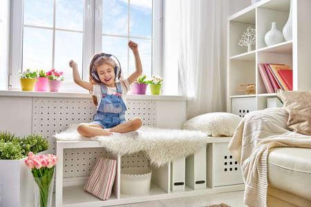 niña con auriculares en casa. Chica niño escuchando música.