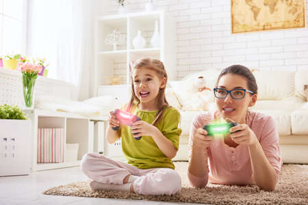 children at play: happy family together. mother and her child girl playing video games. family relax.