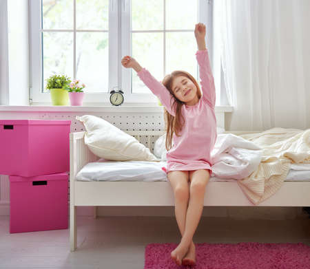 despertarse: Una buena chica ni�o disfruta ma�ana de sol. Buenos d�as en casa. La muchacha del ni�o se despierta de su sue�o. Foto de archivo