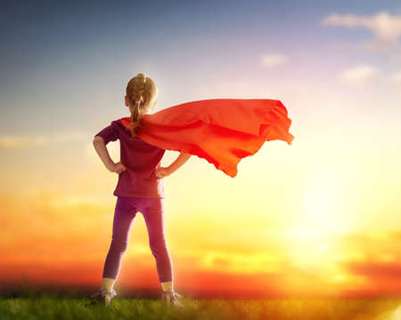 heroes: Little child girl plays superhero. Child on the background of sunset sky. Girl power concept