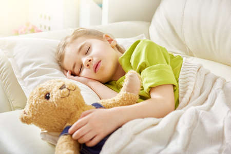 teddies: Adorable little child girl sleeping in the bed with her toy. The child girl hugs the teddy bear.