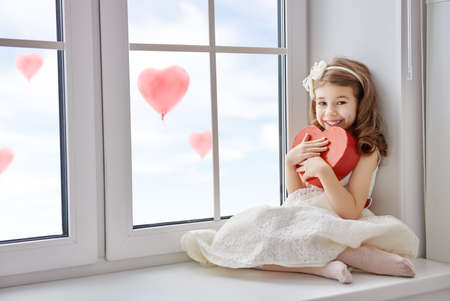 Sweet child girl with red heart. Little girl sitting on the window and holding gift box. Wedding, Valentine concept. Archivio Fotografico