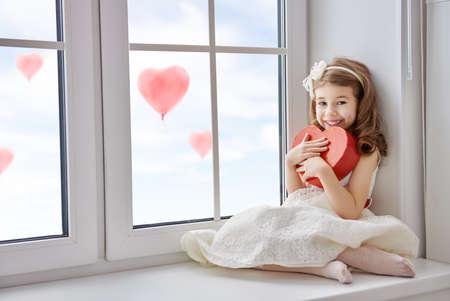 Süßes Kind Mädchen mit roten Herzen. Kleines Mädchen auf dem Fenster sitzt und mit Geschenk-Box. Hochzeit, Valentine Konzept.