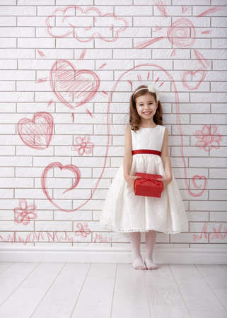 bridesmaid: Sweet child girl with red gift box. Happy little girl with Valentines gift at brick wall painted with childrens drawings. Wedding, Valentine concept.