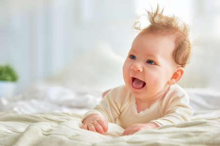 Beau bébé mignon jeune fille souriante sur le lit dans la chambre. Heureux enfant rire.