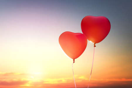 two red balloons in shape of heart on the background of sunset sky. the concept of love and Valentines day. Stock Photo