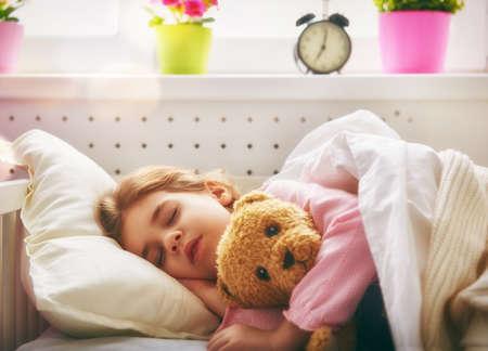 oso blanco: Niña adorable niño durmiendo en la cama con su juguete. La niña abraza el oso de peluche.
