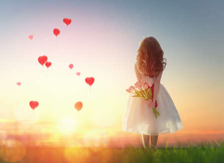 girl in red dress: Sweet child girl looking at red balloons. Little child girl holding bouquet of flowers. Balloons in shape of heart flying in the sunset sky. Wedding, Valentine, love concept.