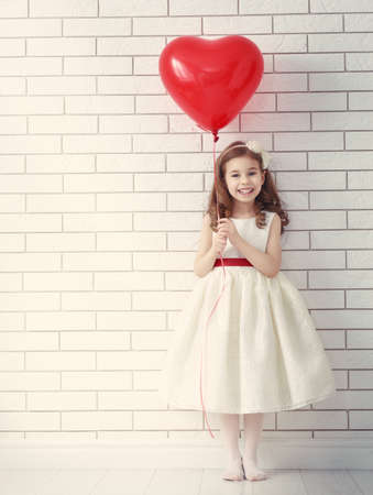 sweet heart: Sweet child girl with red heart. Happy little girl with red balloon at a blank brick wall. Wedding, Valentine concept.