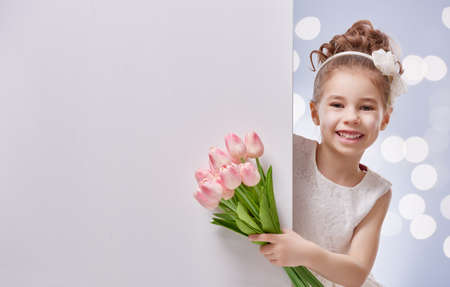 Sweet child girl with white blank poster banner. Happy little girl with bouquet of tulips. Wedding, Valentine, celebration concept.