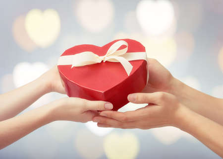 red gift box in shape of heart in hands. the concept of love and Valentines day.
