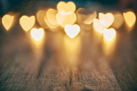 갈랜드는 나무 소박한 배경에 불이 들어옵니다. 마음 발렌타인 배경. 사랑의 개념 및 발렌타인 데이.