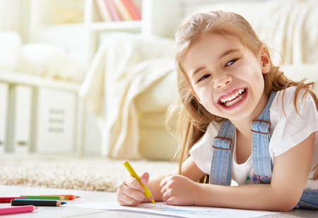 Happy child plays. Little child girl draws with colored pencils. Archivio Fotografico